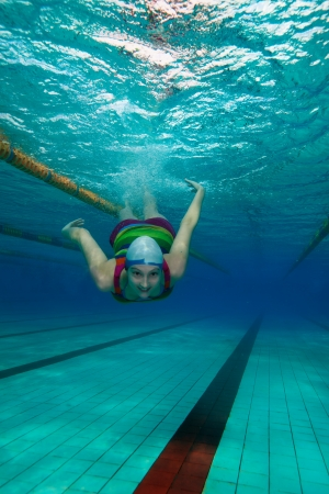 Woman in casual clothes swimming underwater in the pool photo