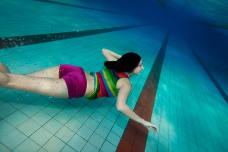 Happy girl in colorful clothes swimming underwater near the pool bottom photo