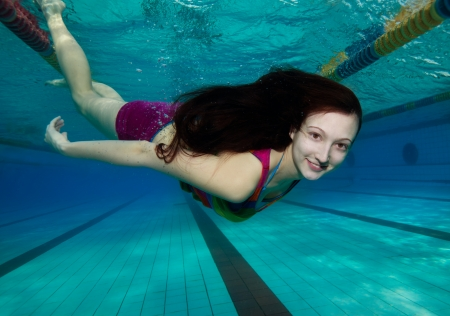 swimming shorts: Young woman with long hair smiling swimming underwater in the pool Stock Photo