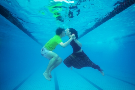 Couple kissing underwater in the pool photo