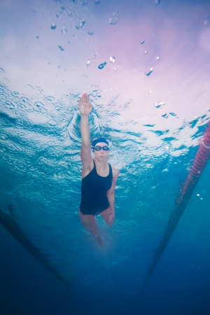underneath: Underwater shoot of a professional woman swimming in crawl style
