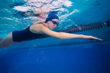 swim goggles: Underwater shoot of a professional sportsman swimming in crawl (stroke) style - shoot side