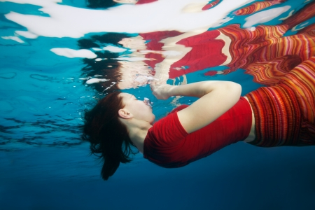 Yong woman  swimming wearing clothes underwater with reflection from surface