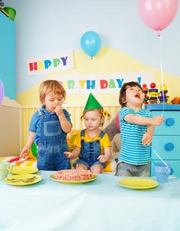 Tres niños comiendo pastel de cumpleaños en la fiesta Foto de archivo - 13948361