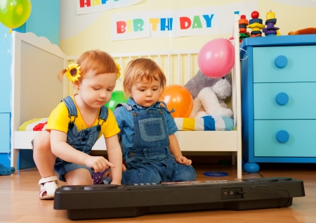 Girl with boy playing piano on birthday party photo