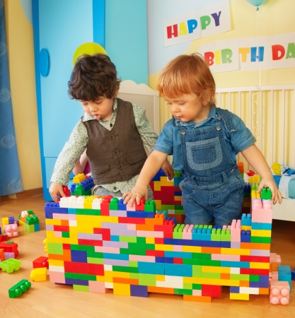 2 3: Kids building a wall of plastic blocks sitting in bedroom Stock Photo