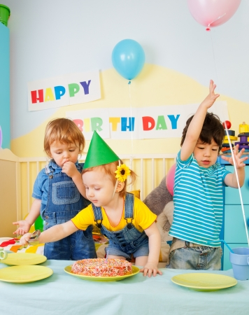 2 years old: Three kids having fun on the birthday party - two boys and one girl Stock Photo