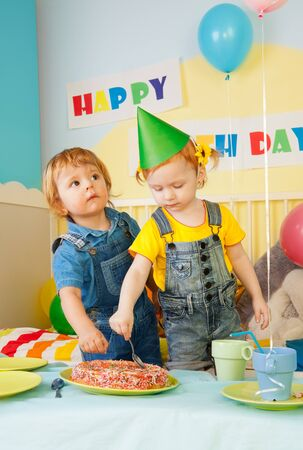 Two kids eating cake on the birthday party - boys and girl photo