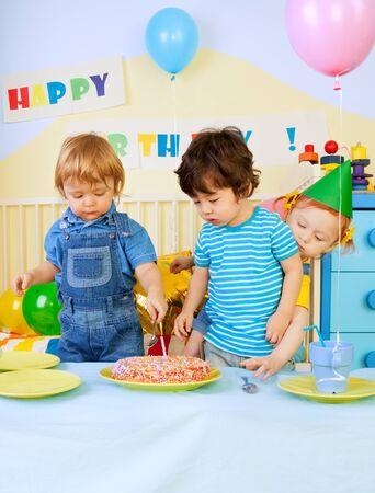 Kids around birthday cake on birthday party - two boys and girl photo