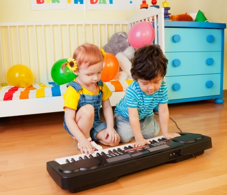 Happy little boy and girl playing a musical instrument photo
