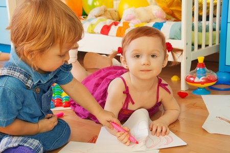 Boy and girl drawing with crayons sitting and laying on the floor photo