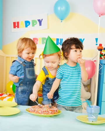 small cake: Three kids eating cake on the birthday party- two boys and one girl
