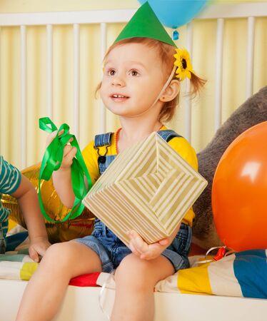 Little girl open the present on her birthday photo