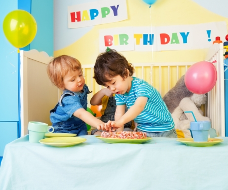 Two kids eating birthday cake at the party photo