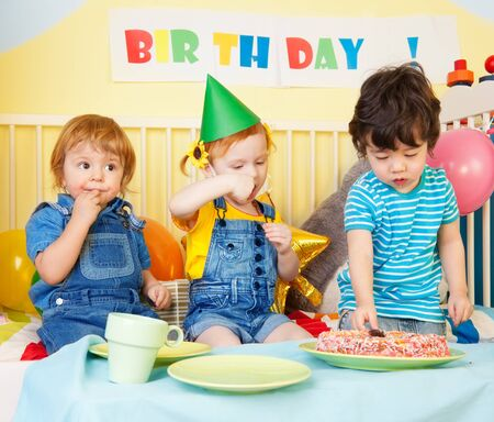 Boys and girl at the birthday party eating cake photo