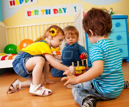 two year old: Two boys and girl playing with toy pyramid puzzle sitting on the floor in bedroom Stock Photo