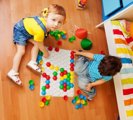 Girls playing with puzzle sitting on the floor in bedroom and looking up photo