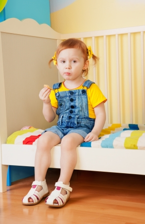 Little girl eat some snacks sitting on the bed in kids birthday photo