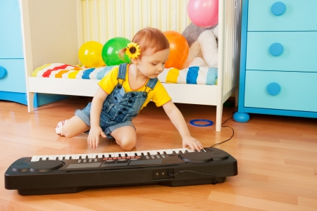 Girl playing piano sitting on the floor in bedroom photo