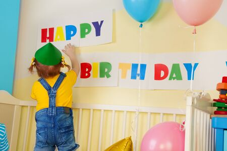 Little girl prepare for birthday party hanging a birthday sign photo