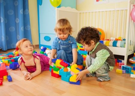 occupied: Kids playing with plastic blocks - two boys and girl