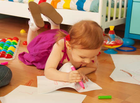 Beautiful girl drawing laying on the floor photo