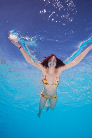 Happy young woman in the water - shot from bellow