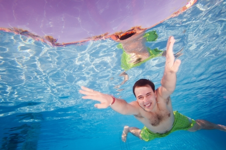 swimming underwater: Happy man diving underwater in the pool with wide smile Stock Photo