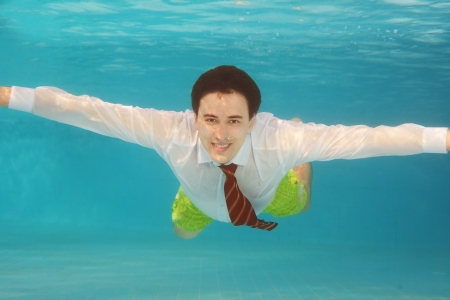 Business man swimming underwater in the pool wearing white shirt and red tie photo