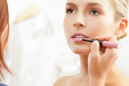 Makeup artist apply pink lipglass on the lips of a model photo