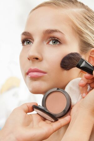 Makeup artist apply blush on cheeks with blush brush photo