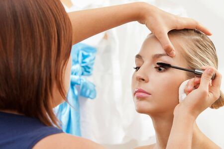 Makeup artist separate and curler lashes with mascara brush photo