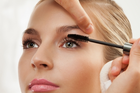 Close-up of separating and curling lashes process with mascara brush photo