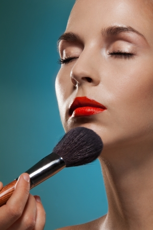 makeup artist: Making up the models face - professional makeup artist working Stock Photo