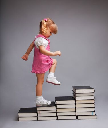 Successfully going from one education level to another - girl going up the stairs of books photo
