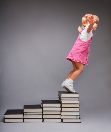 Opportunities after education - girl jumping from steps that symbolize education stages made of books