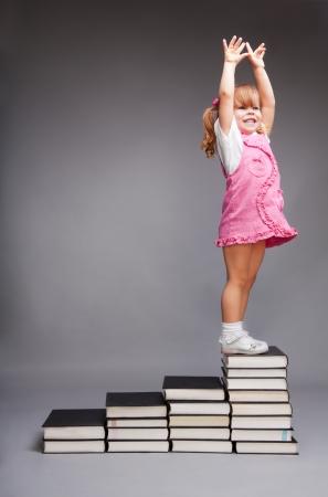 petite fille avec robe: Bonne petite fille debout sur le sommet des livres les étapes Banque d'images