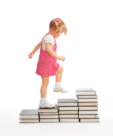 Little girl walk up the educational steps made of books photo