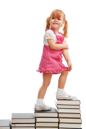 Happy little school girl standing on the steps made of books pile Stock Photo