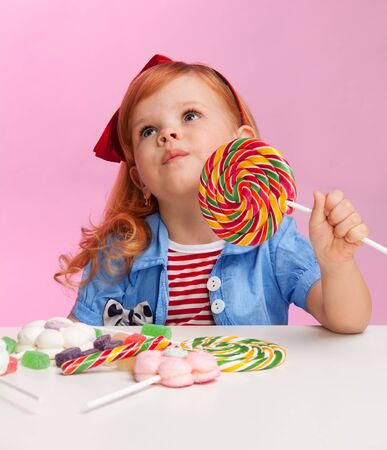 three year old: Thoughtful girl with lollipop witting by the table full of sweets Stock Photo