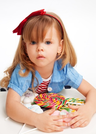 Greedy  girl with pile of sweets laying on the table and with troubled expression on the face photo