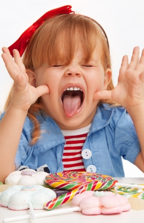 Little girl teasing with hands and having her tongue stick out and mouse open Stock Photo