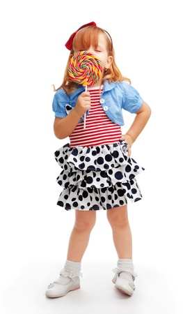 lollypop: Little girl standing and enjoying lollipop that hides her face Stock Photo