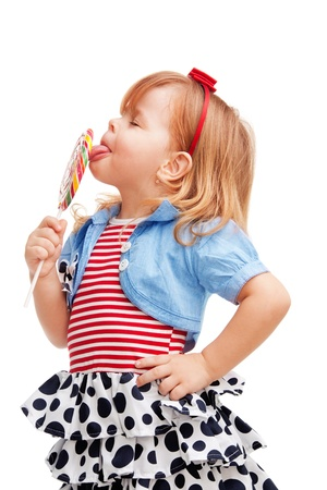 licking in isolated: Little girl standing and licking big lollipop