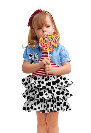 Small girl standing with lollipop, isolated on white photo
