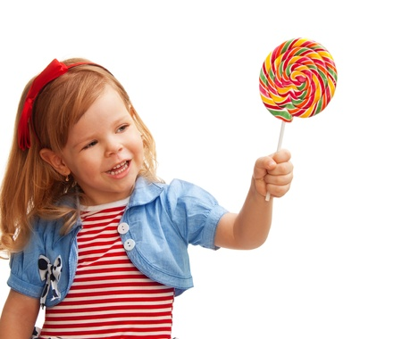 Little girl holds big lollipop in her hand photo
