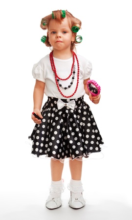 Little girl playing big holding mirror and lipstick, as well as having rollers in her hair photo