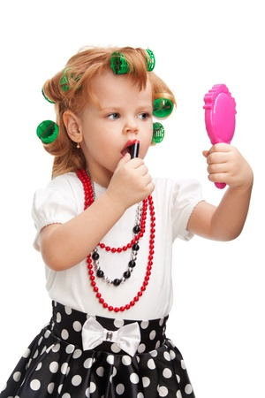 little girl playing to be her mother holding mirror and lipstick and making up her lips photo