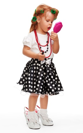 Little girl making up her face with lipstick, playing with mothers things photo