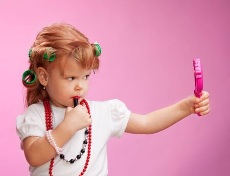 Little girl playing with mothers makeup and holding mirror on pink background photo